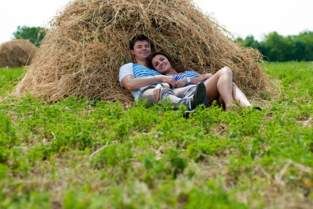 Happy young couple embracing resting on haystack in field on summer day photo