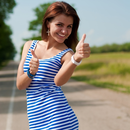 Young happy beautiful woman showing thumbs up outdoors on wide road photo