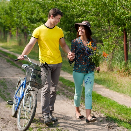 Happy young smiling couple man and woman walking with bicycle on bright summer day photo