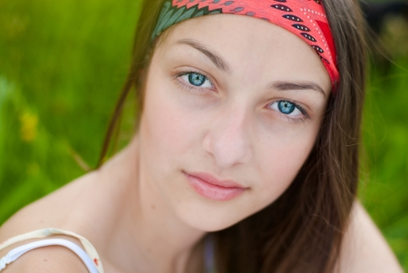 Young beautiful teenage girl with blue eyes portrait on green grass background
