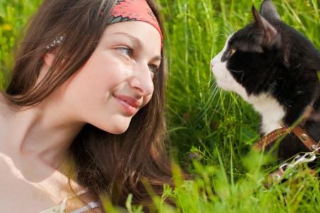 Young beautiful teenage girl with blue eyes portrait on green grass and black cat photo