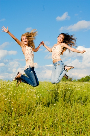 Two happy young women jumping on blue sky and green grass background photo