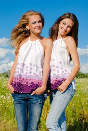 Two happy young women enjoying sun on blue sky background photo