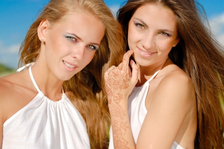 Two happy young women with long blond and brunette hair and bright makeup on blue sky background photo