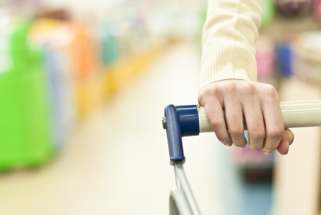 Woman shopping in super market and pushing cart hand closeup photo