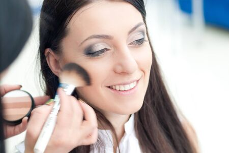 make up artist: Young beautiful happy smiling woman and make up artist applying rouge blush powder