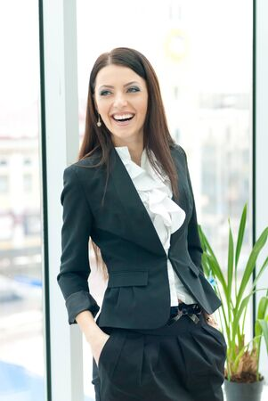 Young happy laughing successfull business female woman in formal suit by office window photo