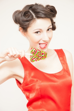 Funny beautiful happy pin up girl in red dress eating lollipop photo