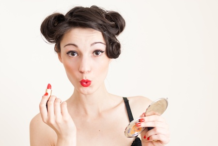 Funny beautiful happy pin up girl holding red lipstick and hand mirror photo
