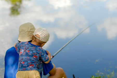 Little toddler boy fishing with father in blue sky reflection