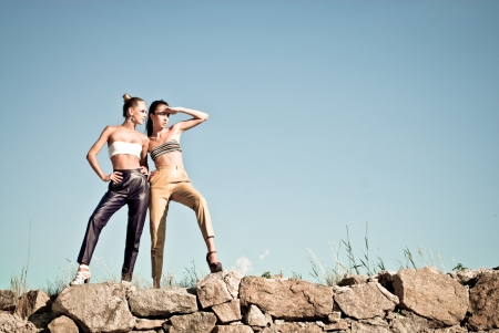 Two fashion girls standing against blue sky and looking far away photo