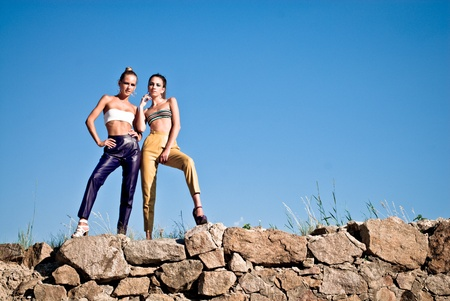 Two beautiful fashion women in leather pants posing against blue sky Stock Photo - 18004041