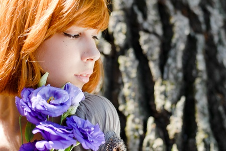 Young beautiful red hair teenage woman model holding purple chinese rose against tree rind photo