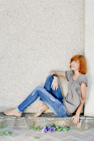 Young beautiful happy redhead teenage woman model girl sitting against wall and looking up on copy space photo