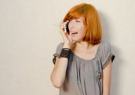 Young beautiful happy redhead teenage woman model girl talking on mobile phone copy space photo