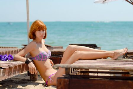 Young beautiful redhead woman model lying on wooden lounge by the sea photo