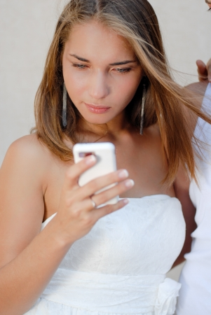 Young beautiful woman in white dress reading message on  touch phone photo