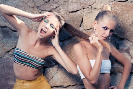 Two young fashion women competing: pulling hair and shouting photo