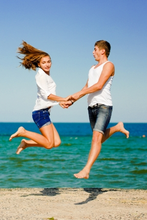 Happy young couple man and woman jumping high by blue sea over blue sky background photo