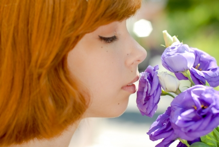 Young beautiful woman smelling purple flower of chinese rose photo
