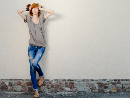 Young beautiful woman in jeans standing near wall  negative space photo