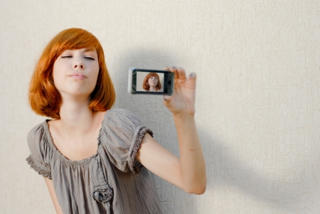self portrait: Young beautiful woman taking picture of herself on mobile touch phone
