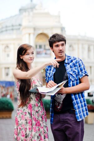 Young couple man and woman looking on map in city centre and showing direction photo