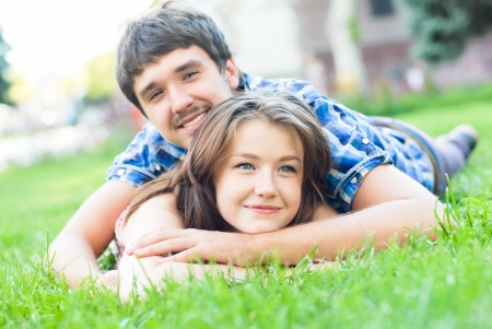 Young happy couple man and woman lying on green lawn and looking up photo