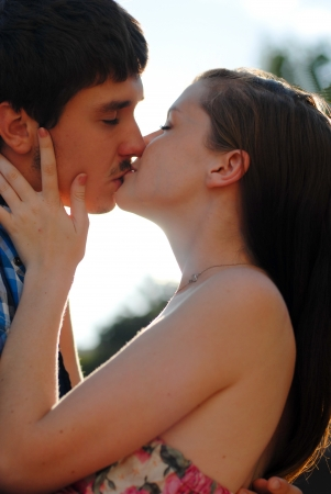 Young happy couple man and woman kissing light flare photo