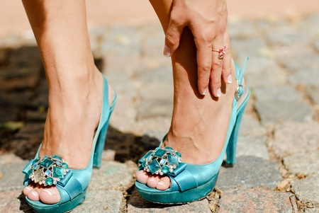 Beautiful legs in blue high heel shoes and hand touching ankle in pain photo