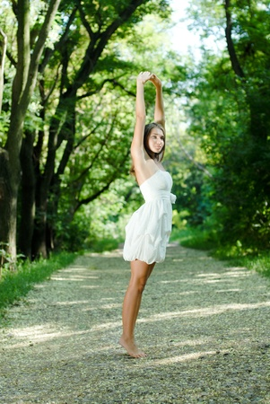 beautifull: Young beautiful woman in white dress standing in green park and stretching hands up