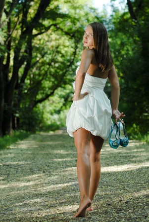 Young beautiful woman in white dress walking in green park with shoes in hand photo