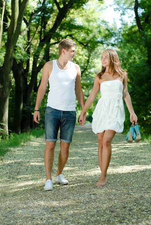 barefoot: Young happy couple man and woman walking in green park holding hands