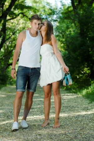 Young happy couple man and woman walking in green park holding hands photo