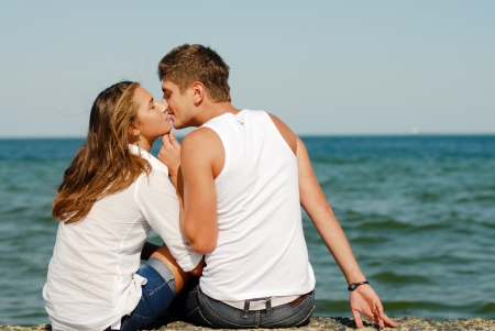 Happy young couple man and woman kissing by blue sea over blue sky background photo