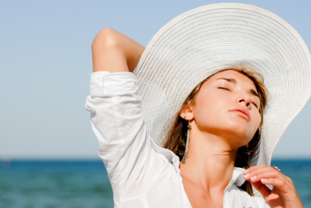 Young beautiful woman sitting by blue sea and wearing white hat photo