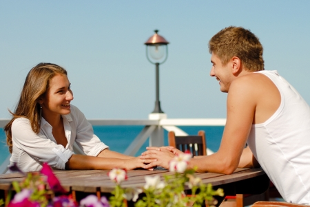 Young happy couple man and woman holding hands and sitting on cafe terrace by the sea photo