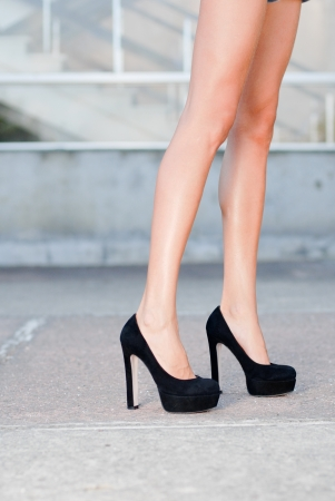 velure: Beautiful silky legs in black high heels shoes outdoor closeup Stock Photo