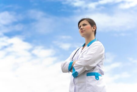beautifull woman: Young happy successful female woman doctor in uniform on blue sky background Stock Photo