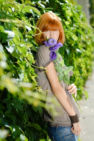 Beautiful redhead teenage girl woman with purple rose by green leaves background photo