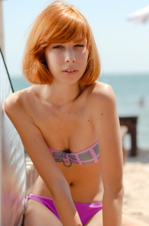 Young beautiful redhead woman model in bikini on sea coast on sunny summer day photo