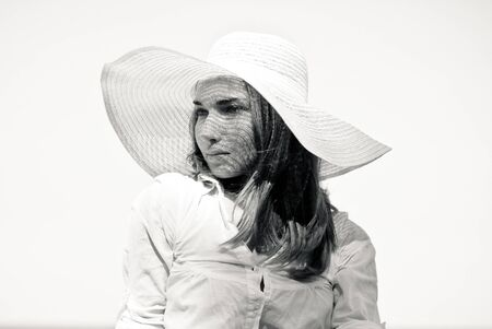Young beautiful woman in white beach hat black and white portrait photo