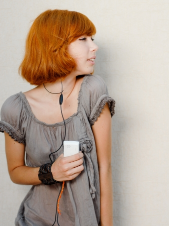 Young beautiful redhead girl listening to music player photo