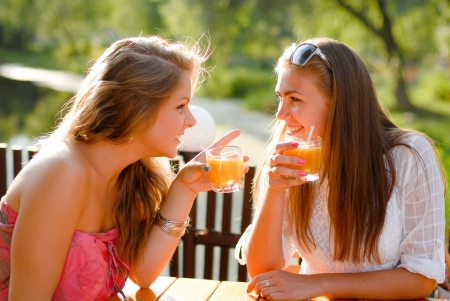Two happy young female women girls friends sitting in terrace cafe and chating photo