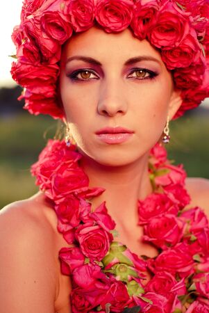 Young beautiful woman with pink roses crown and garland closeup portrait photo