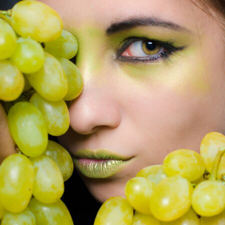 Young beautiful woman holding green grapes closeup portrait on black background photo