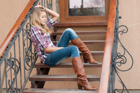 Pretty happy teenage girl woman female sitting on the stairs on sunny autumn day in cowboy hat photo