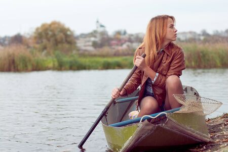 Young woman sitting in boat on autumn day against dull sky and town view landscape photo