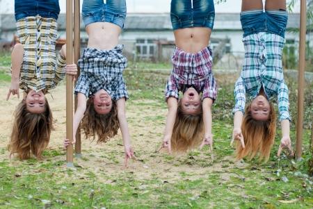 cabeza abajo: Cuatro chicas jóvenes que cuelgan boca abajo en un parque y riendo