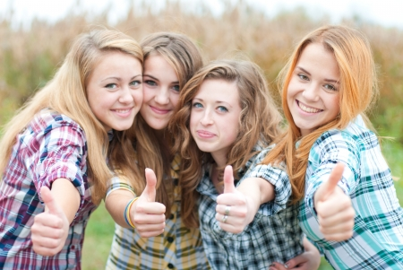 Four happy teen girls friends showing thumbs up photo